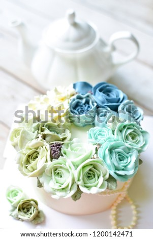 Blue Buttercream flower cake with teapot on wooden background
