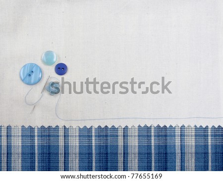 Blue buttons with thread and blue plaid fabric