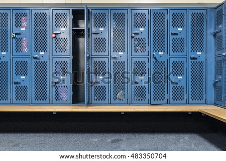 Blue cage lockers in a gym with a bench in front  #483350704