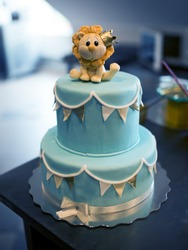 Blue cake with cute lion doll on the top