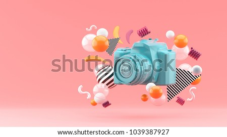 Blue camera surrounded by colorful balls on a pink background.-3d render. stock photo