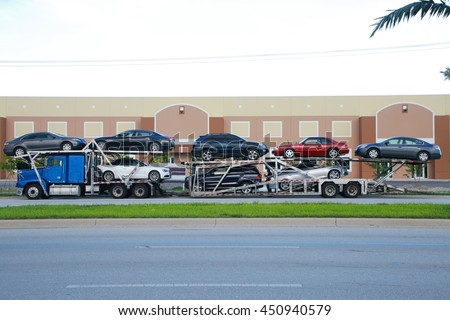 Blue Car Carrier Truck with Various Makes Models and Colors of Cars Parked on the Side of the Street with Green Grass and the Road Below and Brown Industrial Building Above in the Background #450940579