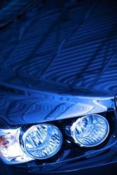 Blue Car Concept Photo. Blue Body Compact Car Hood and Headlight Closeup.