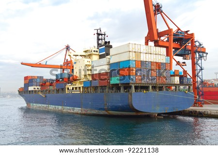 Blue cargo ship in port, fully loaded with containers