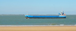 Blue cargo ship sailing to Antwerp port by the coast of Vlissingen, Netherlands. Freight transportation, nautical vessel, logistics, industry, commerce, environment. Panoramic view, copy space