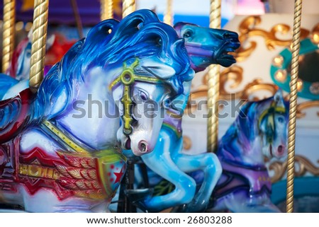 Blue carousal horses on a carnival merry-go-round.