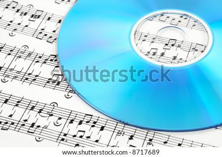 Blue CD or DVD on sheet music. Digital music concept.
