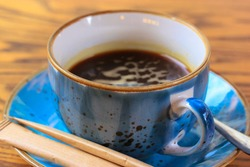 Blue ceramic cup on a saucer with black coffee close up on a beautiful brown wooden background. A mug with hot non-alcoholic beverage. Breakfast caffeine drink flatly, top view. Sugar sticks, a spoon.