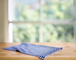 Blue checked tablecloth on wood with blur green bokeh from window kitchen background.Summer and picnic concepts.Design for key visual food and drink products.