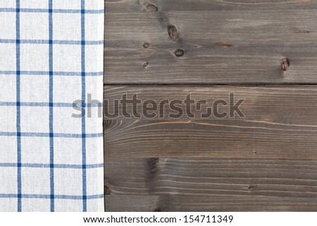 Blue checker tablecloth on brown vintage wooden table background
