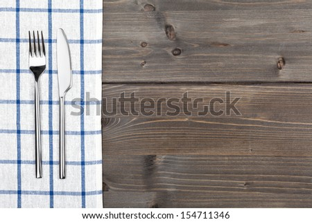 Blue checker tablecloth on brown vintage wooden table background with silverware