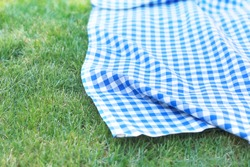 Blue checkered towel on grass,gingham napking outdoor.Product advertisement display.Green grass  picnic cloth top view background.Food promotion design backdrop.