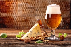 Blue cheese appetizer and beer on brown vintage background and space for text