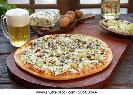 Blue cheese pizza with a glass of beer and some ingredients