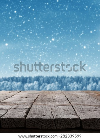 Blue Christmas background with trees and snow with wooden floor