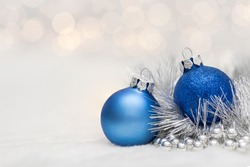 Blue Christmas ball with garland. Bokeh effect on white background. Copyspace for your greeting or wishes