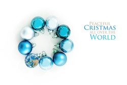 blue Christmas balls and an earth globe in a circle, isolated with shadows on a white background,  text Peaceful Christmas all over the World, one element provided by NASA, flat top view from above