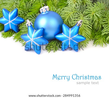 Blue Christmas balls and stars on branches of a Christmas tree on a white background. Christmas background.