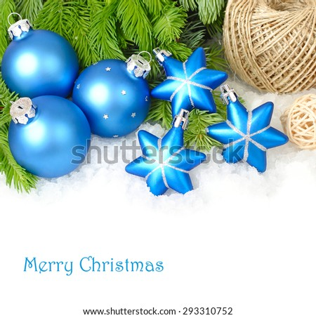 Blue Christmas balls and stars on branches of a Christmas tree on snow on a white background. A Christmas background with a place for the text.