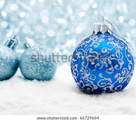 Blue christmas balls on the snow over blurry background, shallow depth of field