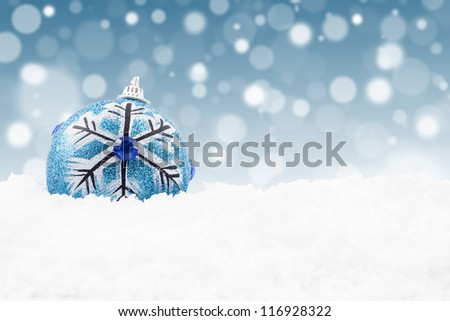 Blue christmas bauble on the snow with christmas lights background