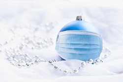 Blue Christmas bauble with blue surgical face mask on white background and silver chain decorations