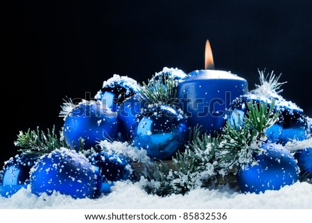 blue christmas baubles and candle in the snow on black background