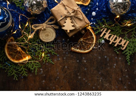 Blue christmas. gift in craft wrapping paper, ribbon, christmas balls. presents on dark wooden table  #1243863235