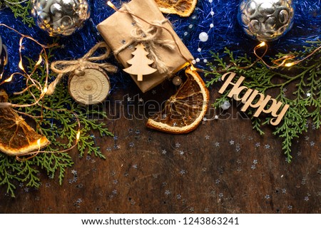 Blue christmas. gift in craft wrapping paper, ribbon, christmas balls. presents on dark wooden table  #1243863241