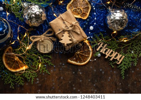 Blue christmas. gift in craft wrapping paper, ribbon, christmas balls. presents on dark wooden table  #1248403411
