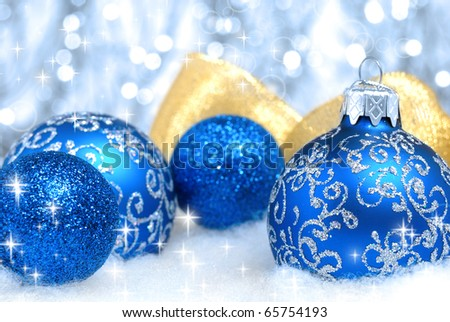 Blue christmas tree balls and golden ribbon over blurry background. Shallow depth of field