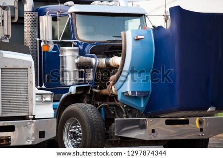 Blue classic American bonnet big rig semi truck with open hood standing on the parking lot for repair engine and schedule maintenance service work to ensure reliable operation during the voyage