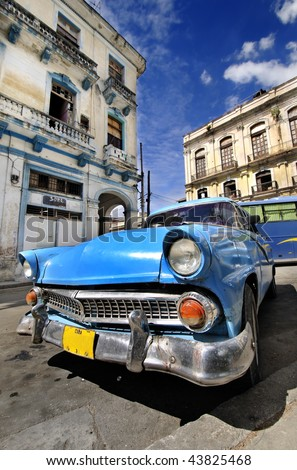 Blue classic american car in havana street with eroded buildings in the background
