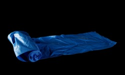 Blue clean plastic garbage bag roll isolated on black background