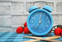 Blue clock, cherrry tomato and wooden fork  on brick wall background are symbiric of diet concept, Intermitten fasting