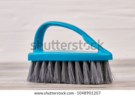 Blue clothes brush with a handle. Close up blue plastic brush on wooden background. House cleaning product. #1048901207
