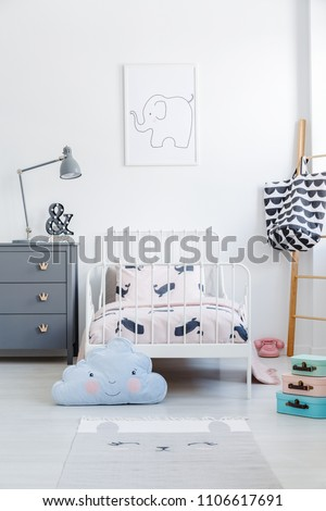 Blue cloud pillow in front of white bed next to grey cabinet in kid\'s bedroom interior. Real photo