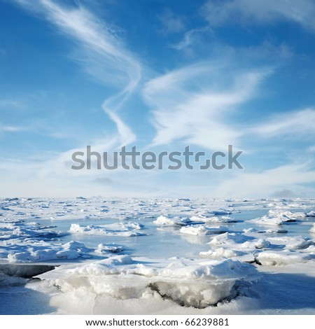 Blue clouds and frozen water. Winter landscape