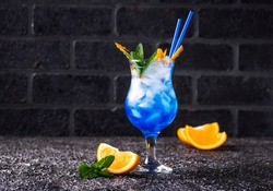 Blue cocktail drink with ice, mint and orange