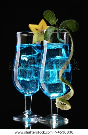 Blue cocktail in glasses on black background