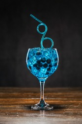 Blue cocktail with blueberry and ice in a glass on wooden table.