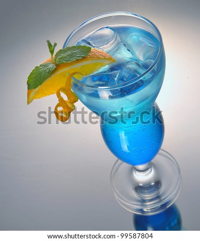 blue cocktail with ice and orange on gray and reflecting