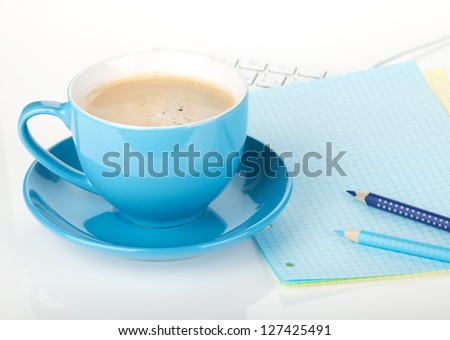 Blue coffee cup and office supplies. Closeup on white background