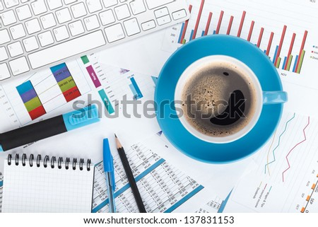 Blue coffee cup on financial papers, computer and office supplies