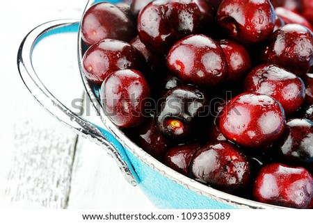 Blue colander filled with fresh black cherries over a rustic background. - stock photo