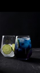 Blue cold drink in a transparent glass on a black background in a dark key, the second glass is out of focus with ice and a piece of lime, vertical background