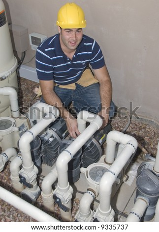 blue collar worker inspecting pool filter pumps