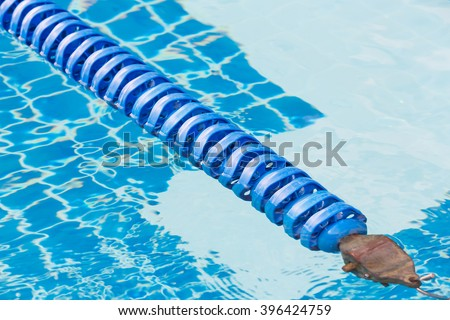 Blue color plastic swimming pool lane rope floating on water ...