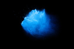 Blue color powder explosion cloud on black background.Closeup of Blue dust particles exhale on dark background.