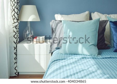 Blue color scheme bedding and white table lamp with natural light from a window